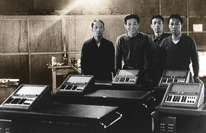 Эпохальное событие: братья Тосио, Казуо, Тадао и Юкио Касио (на фото — слева направо)  представляют первую серийную партию калькулятора Casio 14-A (1957 г.)