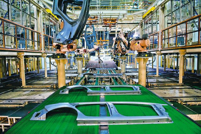 Роботы с вакуумными присосками устанавливают панели кузова на распределительные стойки